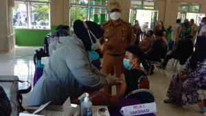Camat Lubuk Begalung, Heriza Syafani mendampingi peserta vaksin termuda di hari pertama gebyar vaksinasi Covid-19 di Kecamatan Lubuk Begalung, Selasa (2/8/2021) pagi. (Foto: Dok. Istimewa)