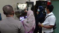 Polisi memeriksa rekaman kamera pengawas bersama N, 23 tahun yang membuat laporan palsu. (Foto: Dok. Polresta Padang)