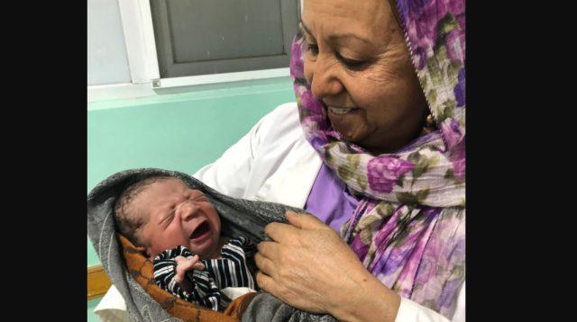 Fauzia Raouf, bidan senior di Rumah Sakit 100 Tempat Tidur, dengan seorang bayi laki-laki berusia beberapa jam. Seperti banyak rumah sakit umum, rumah sakit ini menghadapi kekurangan staf dan obat-obatan. (Pamela Constable/The Washington Post)